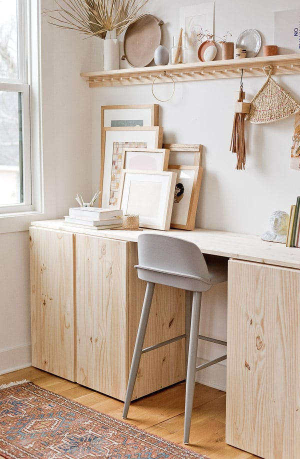 A wood desk with storage cabinets underneath with grey stool underneath.