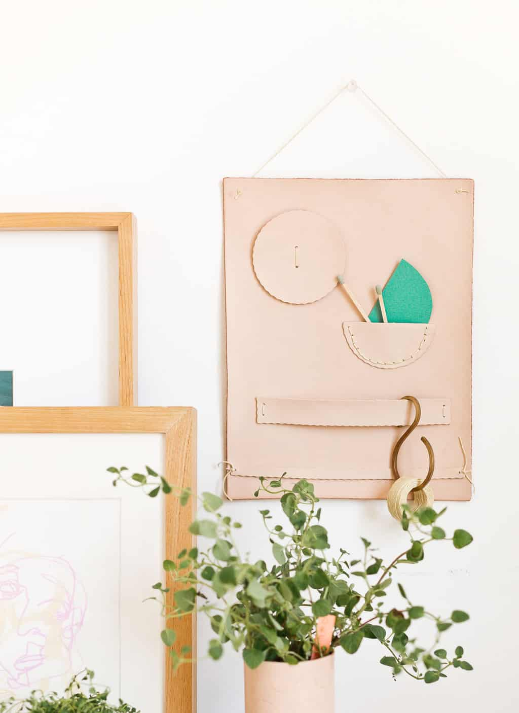 A leather wall organizer hangs on the wall with plants surrounding it.