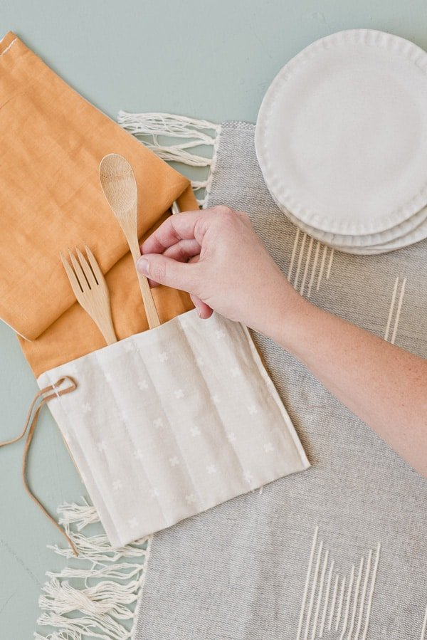 Hand reaching into frame to grab wooden utensil from DIY fabric utensil wrap.