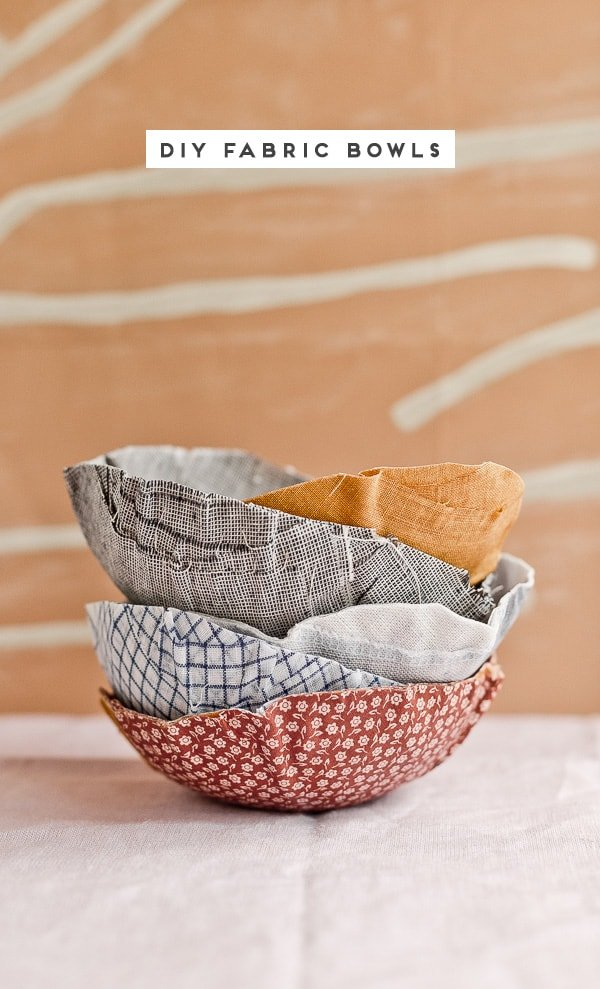 Stacked DIY fabric bowls on a table with abstract wallpaper backdrop.