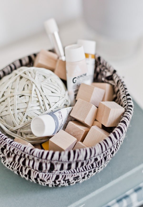Image of a handmade yarn bowl with craft supplies being stored inside.
