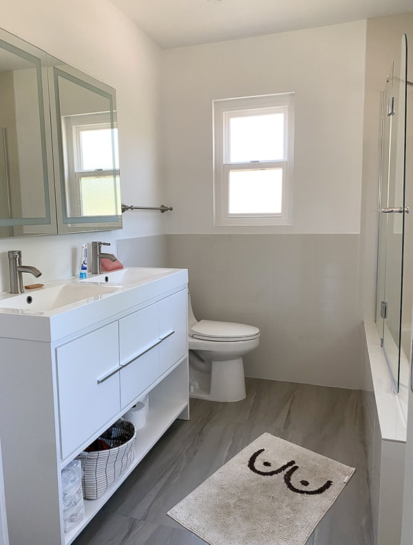 Before photo of basic rental bathroom with white vanity.