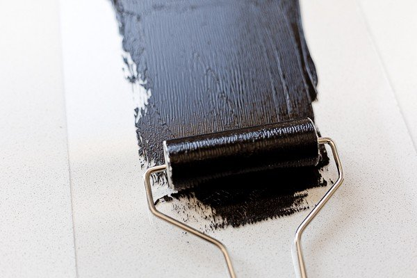 Rolling out black block printing ink onto a plexiglass palette, to prepare for inking lino block.