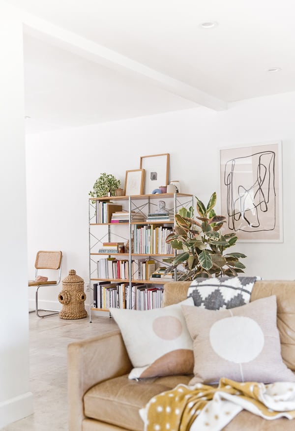 mid-century book shelf with books and decorative objects in a neutral living room