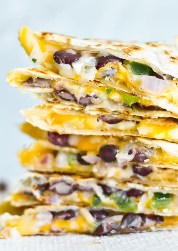 Super closeup view of cheesy black bean quesadillas, stacked up on a plate.