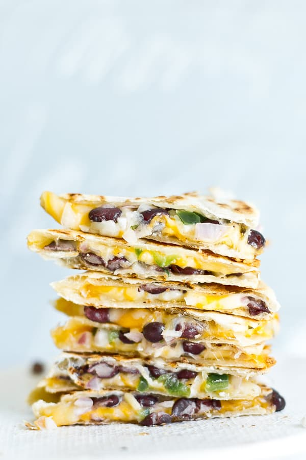Closeup image of cheese and black bean quesadillas, stacked on each other.