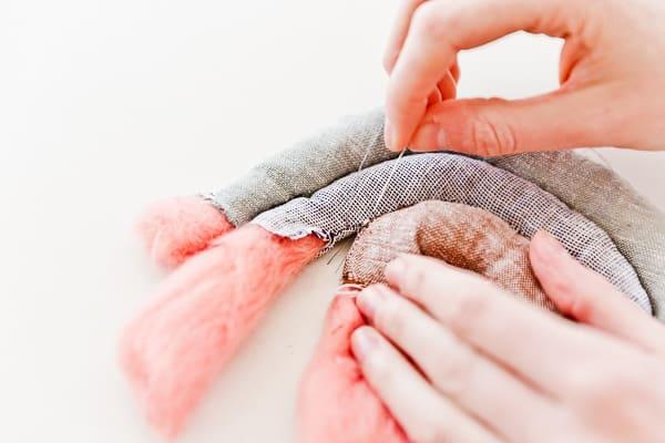 Stitching together a fabric rainbow plush toy.