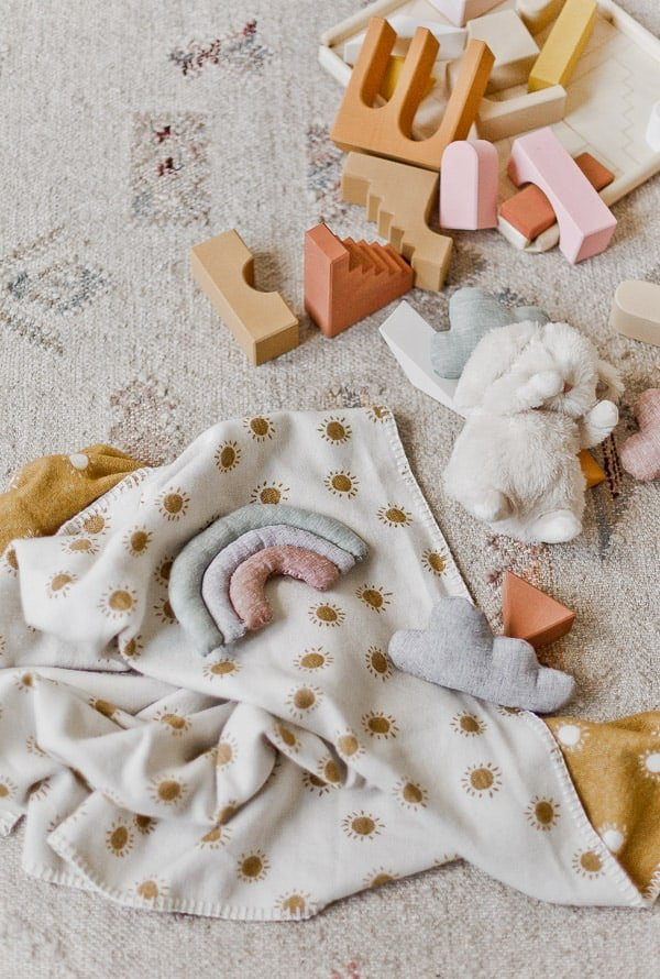 Toys on the ground in a child's room. Neutral colors and textures.