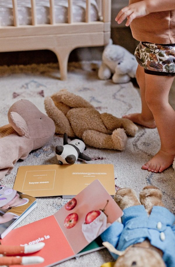 Photo of colorful board books on the ground with toys surrounding it.