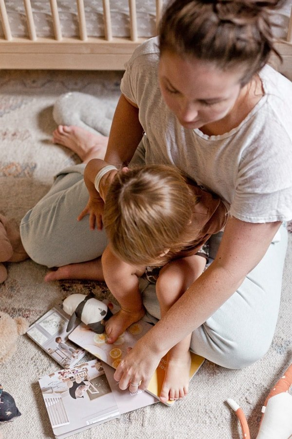 Photo of mother and child reading books in a nursery, on the floor.
