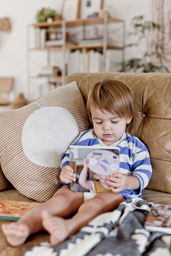 Photo of toddler reading a small book on the couch, about toys.