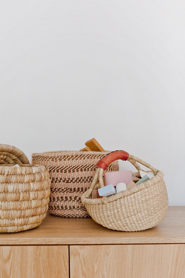 There woven baskets, sitting on top of a credenza, with toys inside.