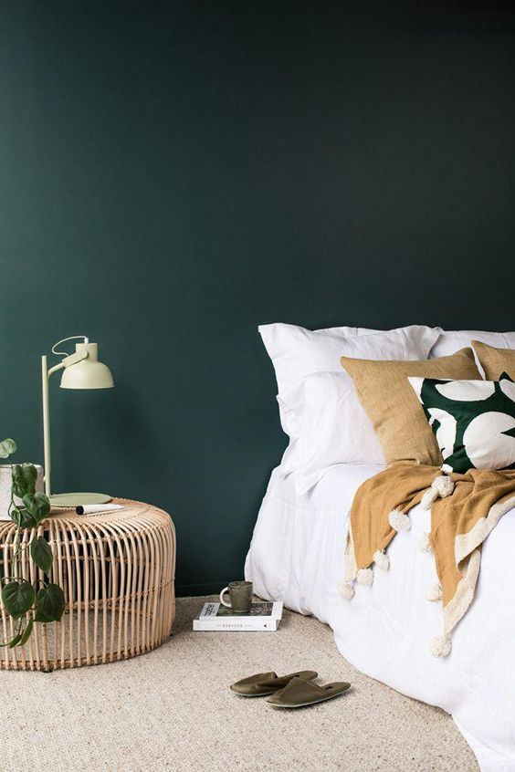A moody green (almost forest green meets teal) color bedroom with white bedding.