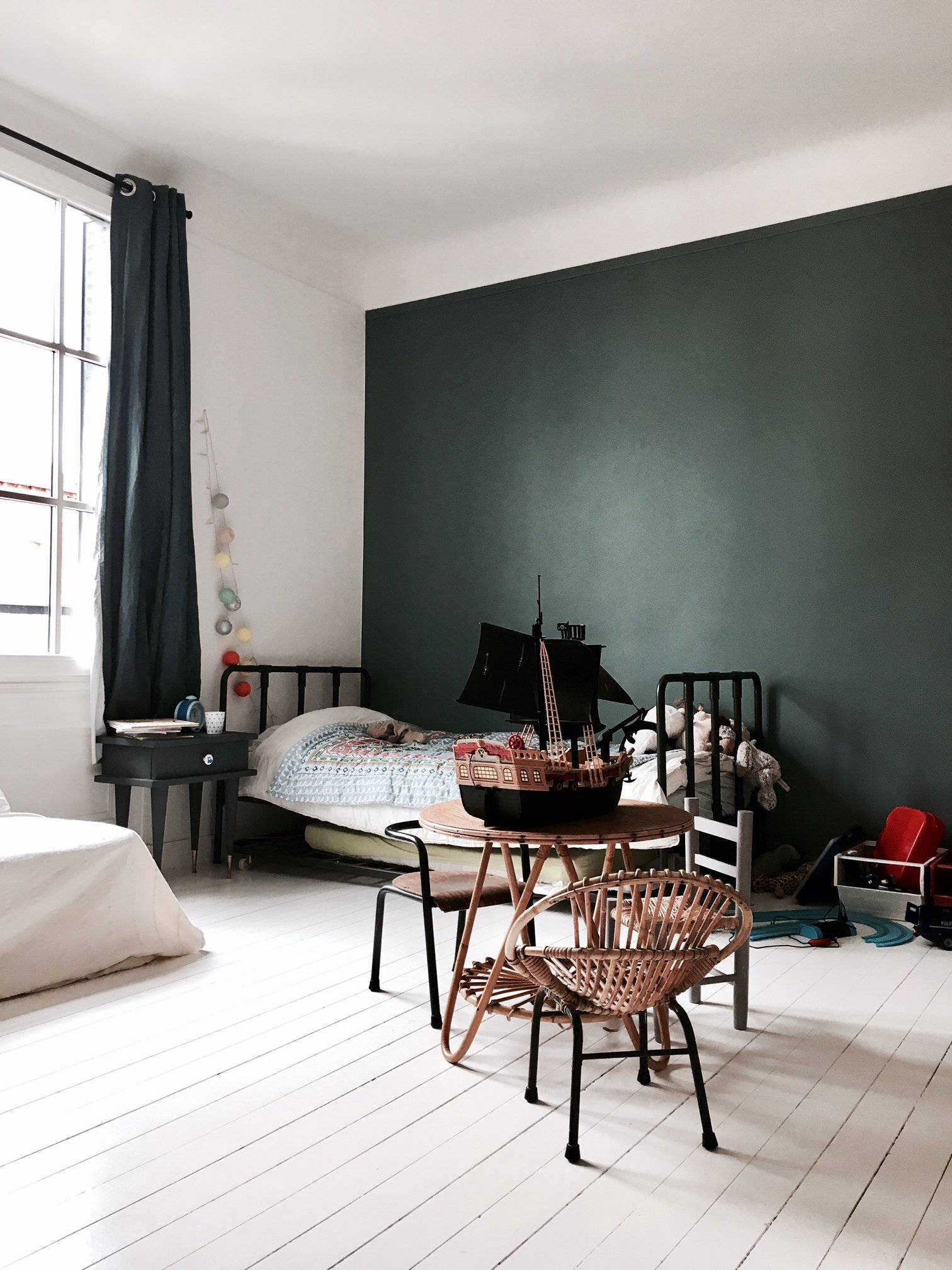 A green accent wall in a cute, modern kid's room.