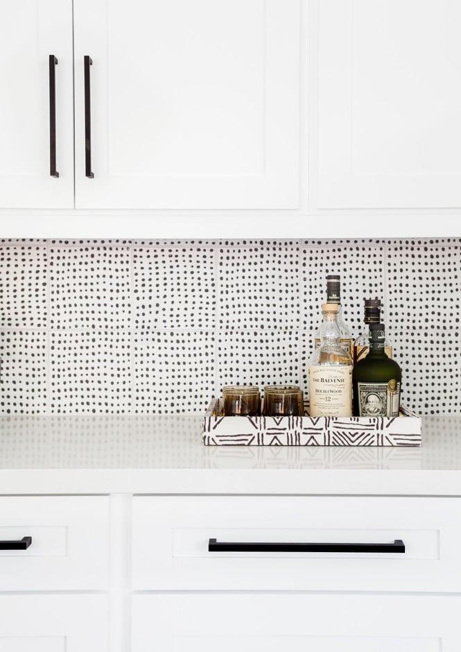 Black and white wallpaper pattern as backsplash in kitchen