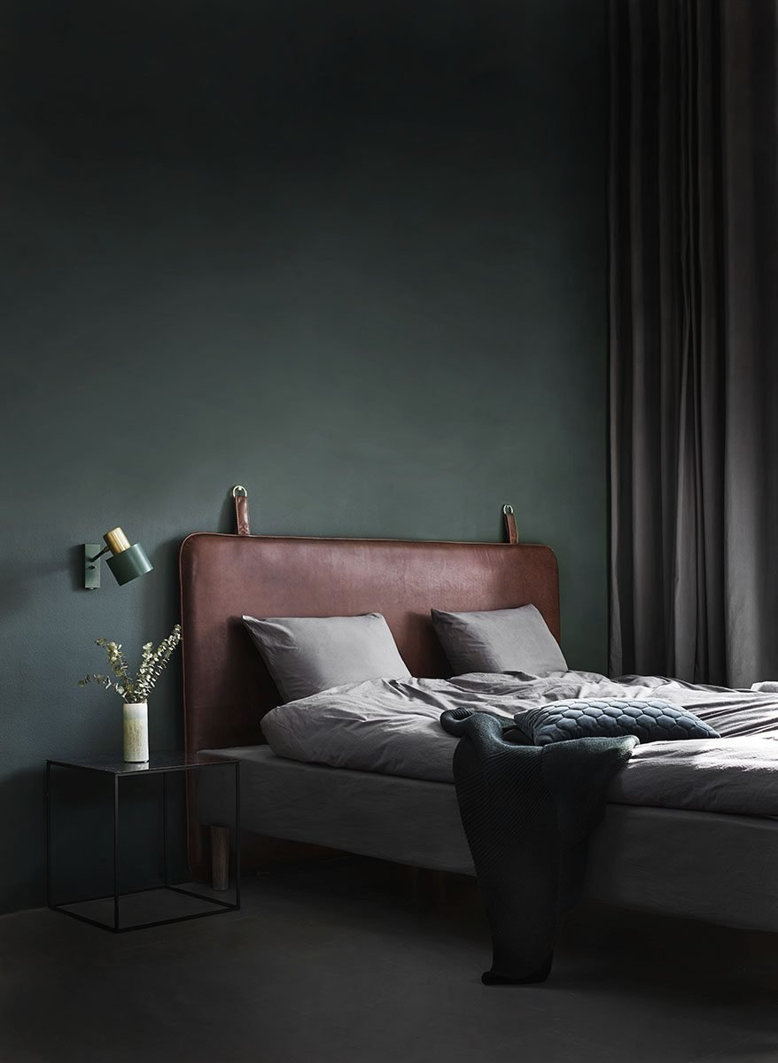 A moody green bedroom with leather headboard and minimal modern decor.
