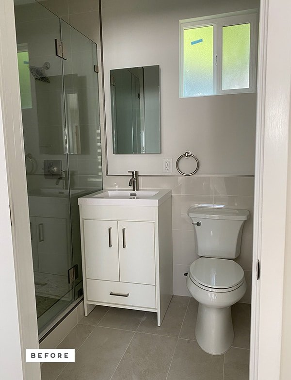 Photo of 'before' basic builder grade bathroom with white vanity and toilet.