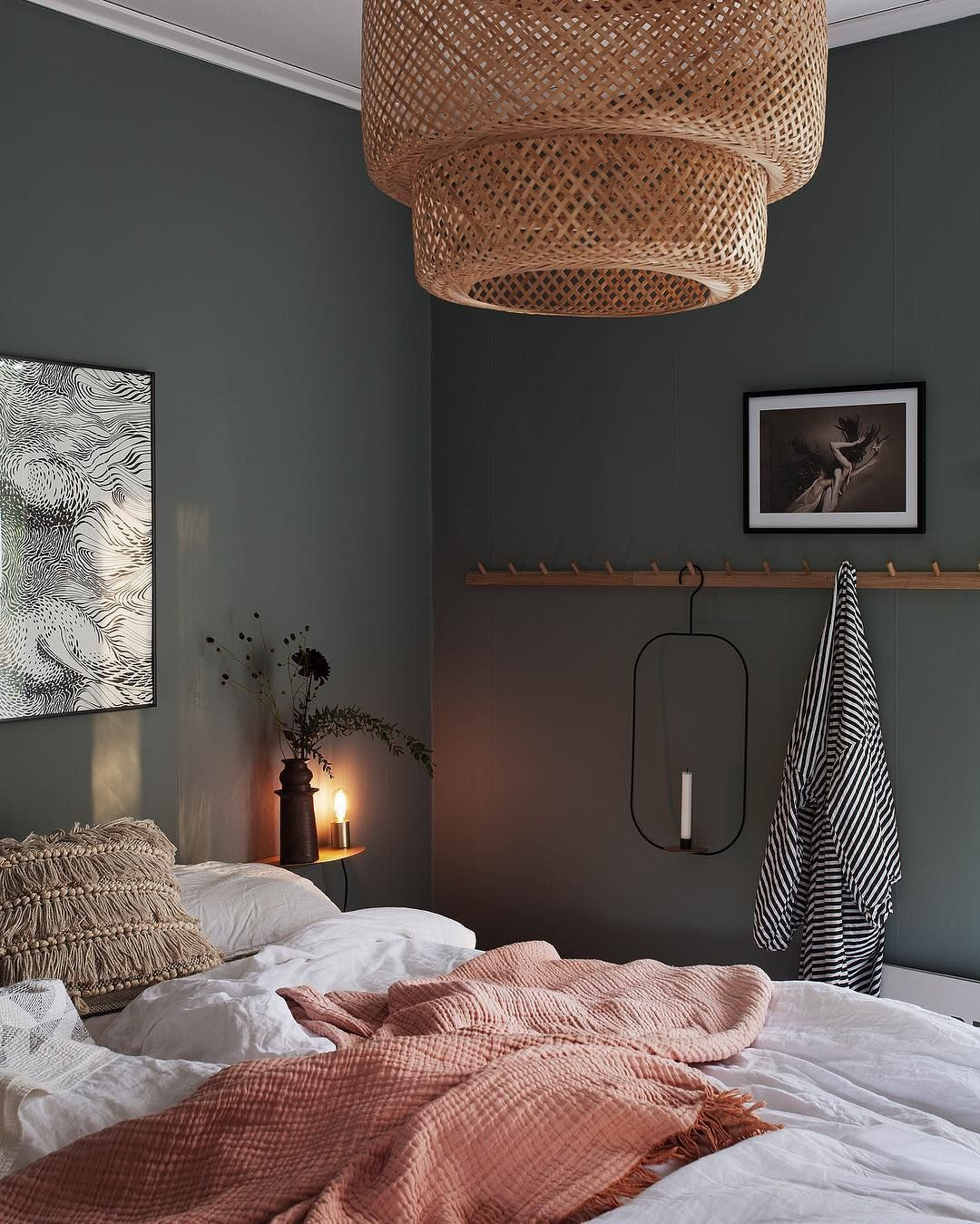 A moody green bedroom with natural wood accents.