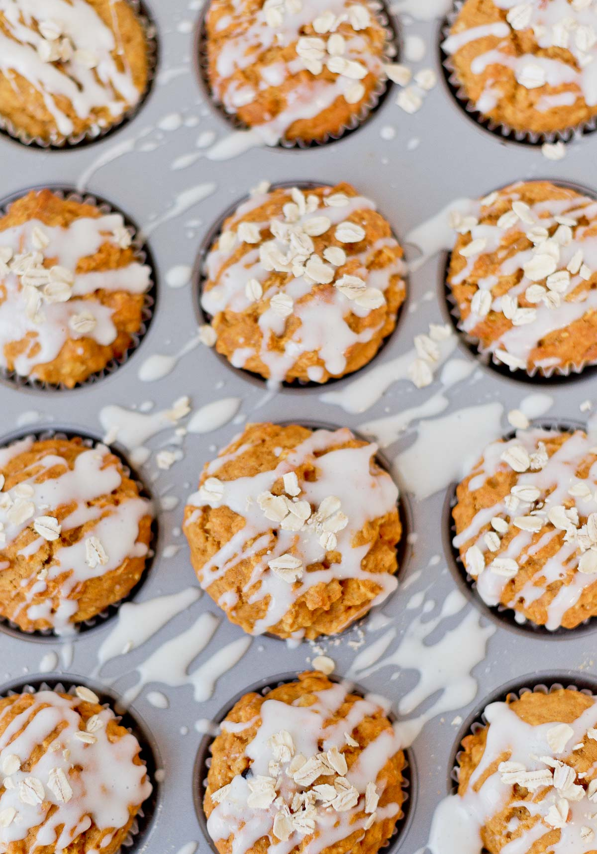 Pumpkin muffins with a cream cheese glaze and oats sprinkled on top.