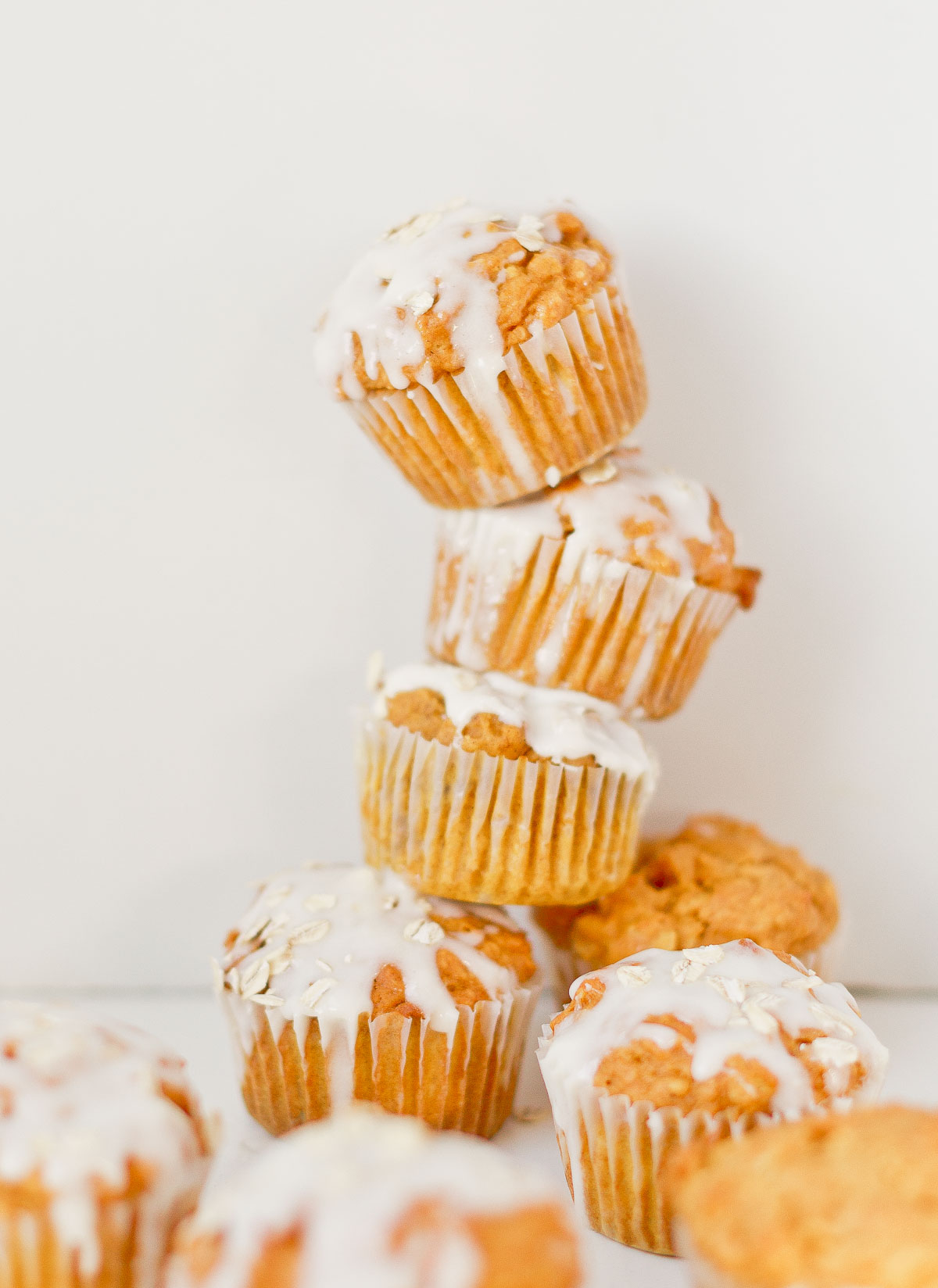 Pumpkin muffins stacked on top of each other, with a cream cheese glaze and oats sprinkled on top.
