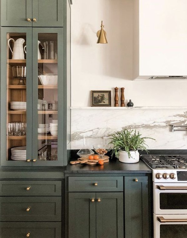 Green cabinets and brass hardware with soapstone counters.