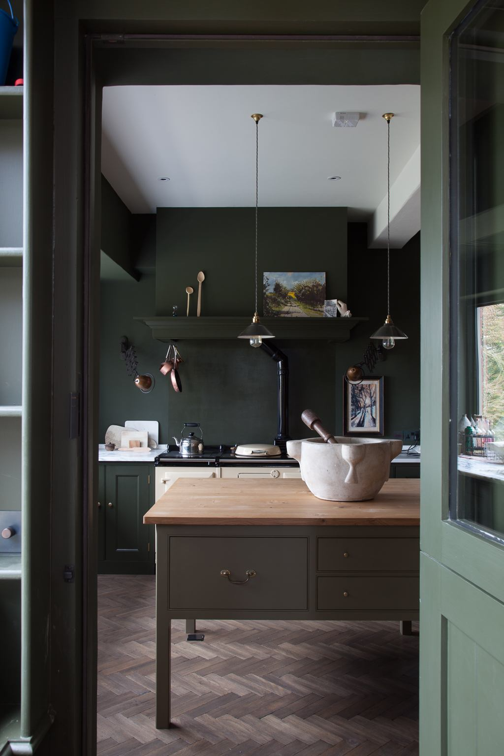 Moody green kitchen with wooden island and herringbone floors.