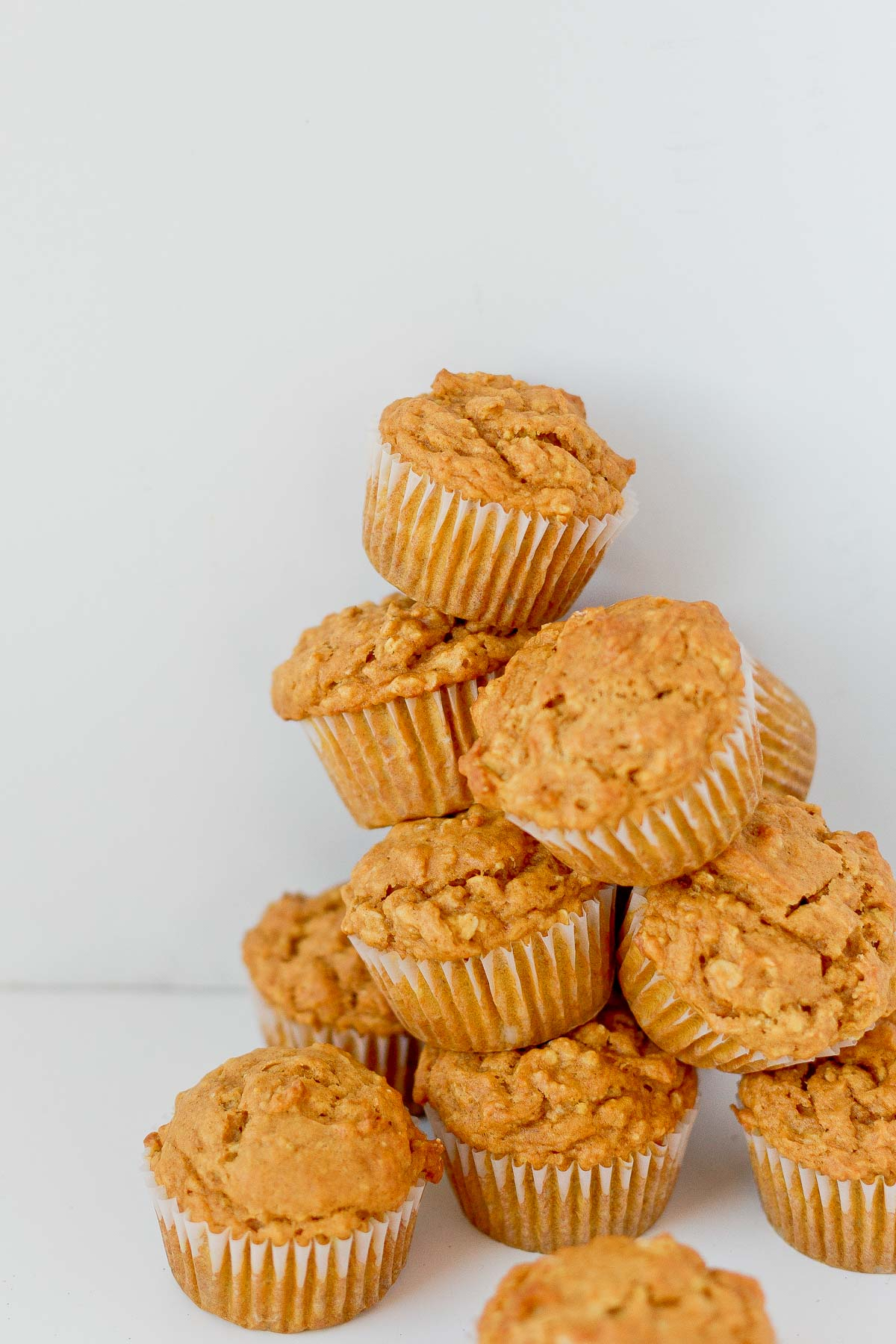 Pumpkin oat muffins stacked on top of each other.