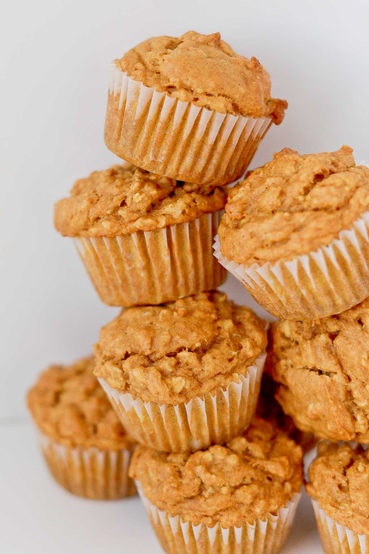 Pumpkin oat muffins stacked on top of each other, close up.