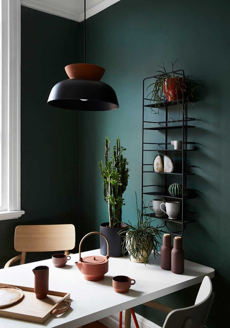 Moody green walls in a cozy dining room.