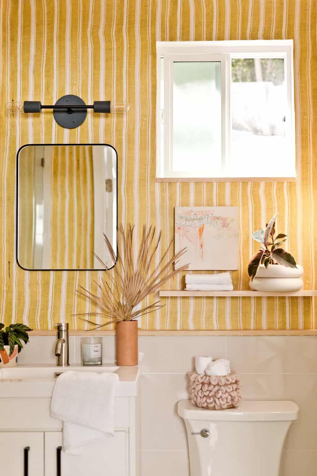 Yellow striped bathroom with black modern accents and natural elements.