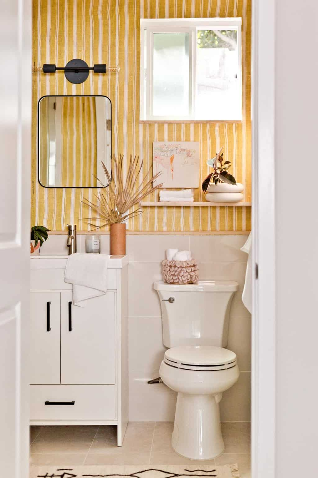 Yellow striped bathroom with white vanity and black, modern accents.