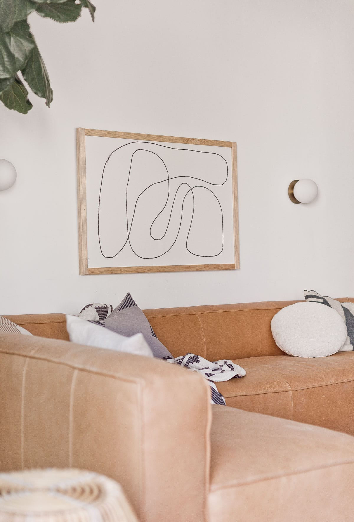 Photo of leather sectional from Article with neutral pillows and abstract artwork.