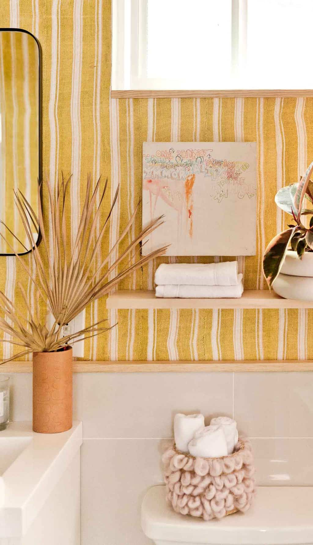 Photo of yellow striped bathroom makeover with floating shelf.