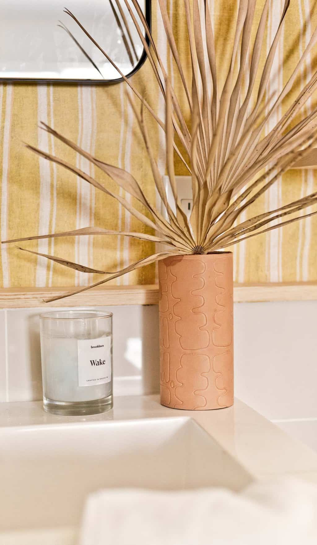Embossed leather vase with funky pattern in a striped, colorful bathroom.