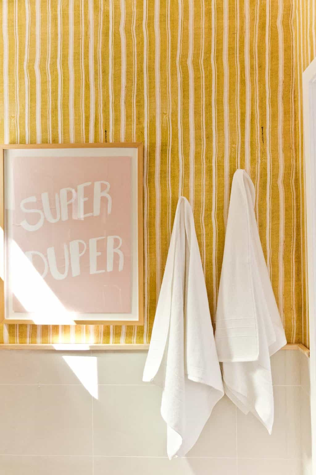 Super Duper graphic artwork in bold bathroom with stripes.