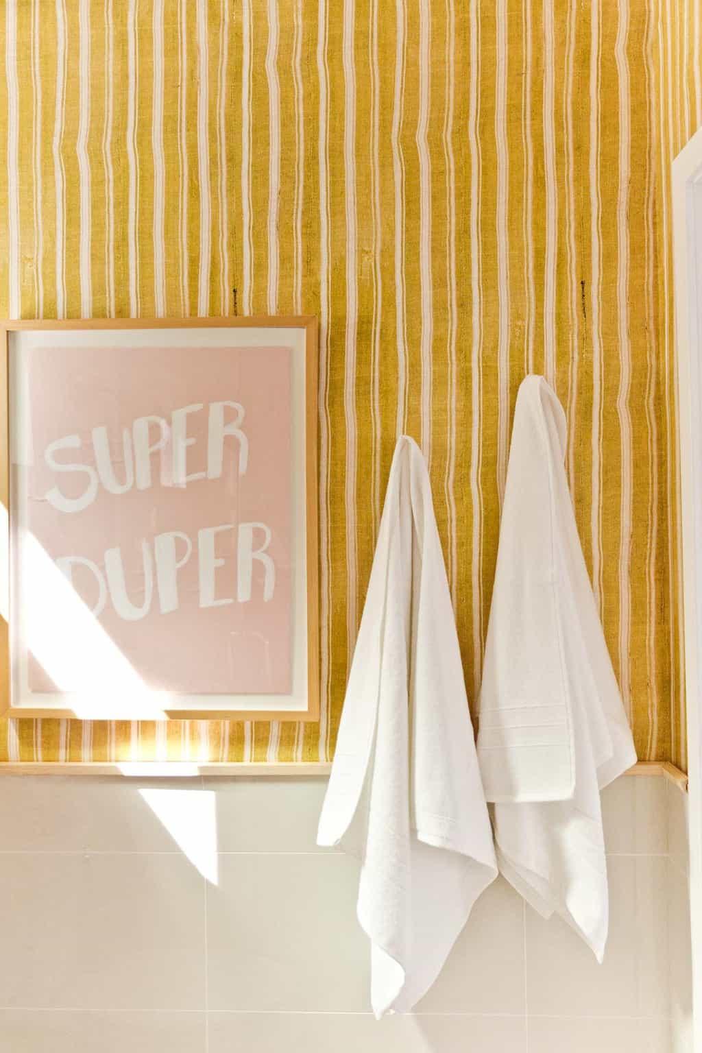 Super Duper graphic artwork in bold bathroom with stripes.