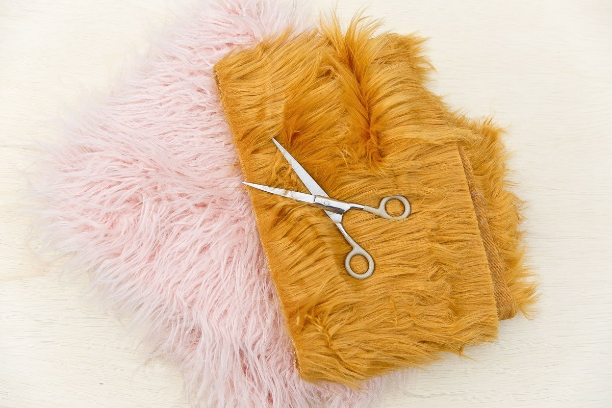 Pink and yellow fur fur with scissors stacked on top.