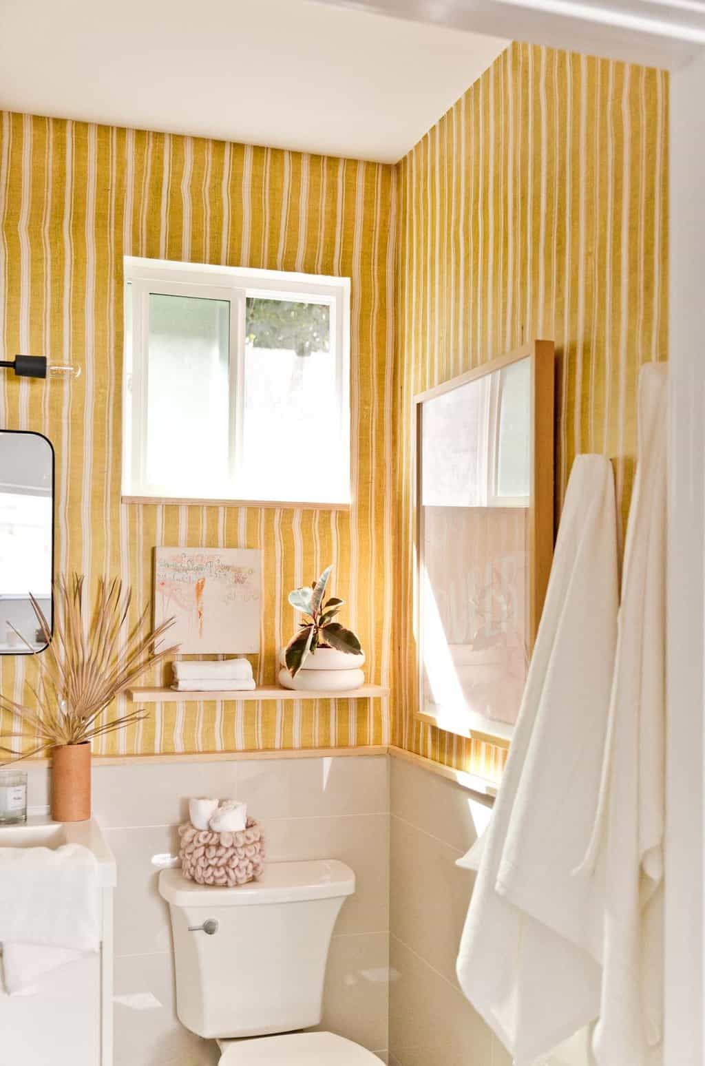 Image of a modern, yellow bathroom with striped wallpaper.