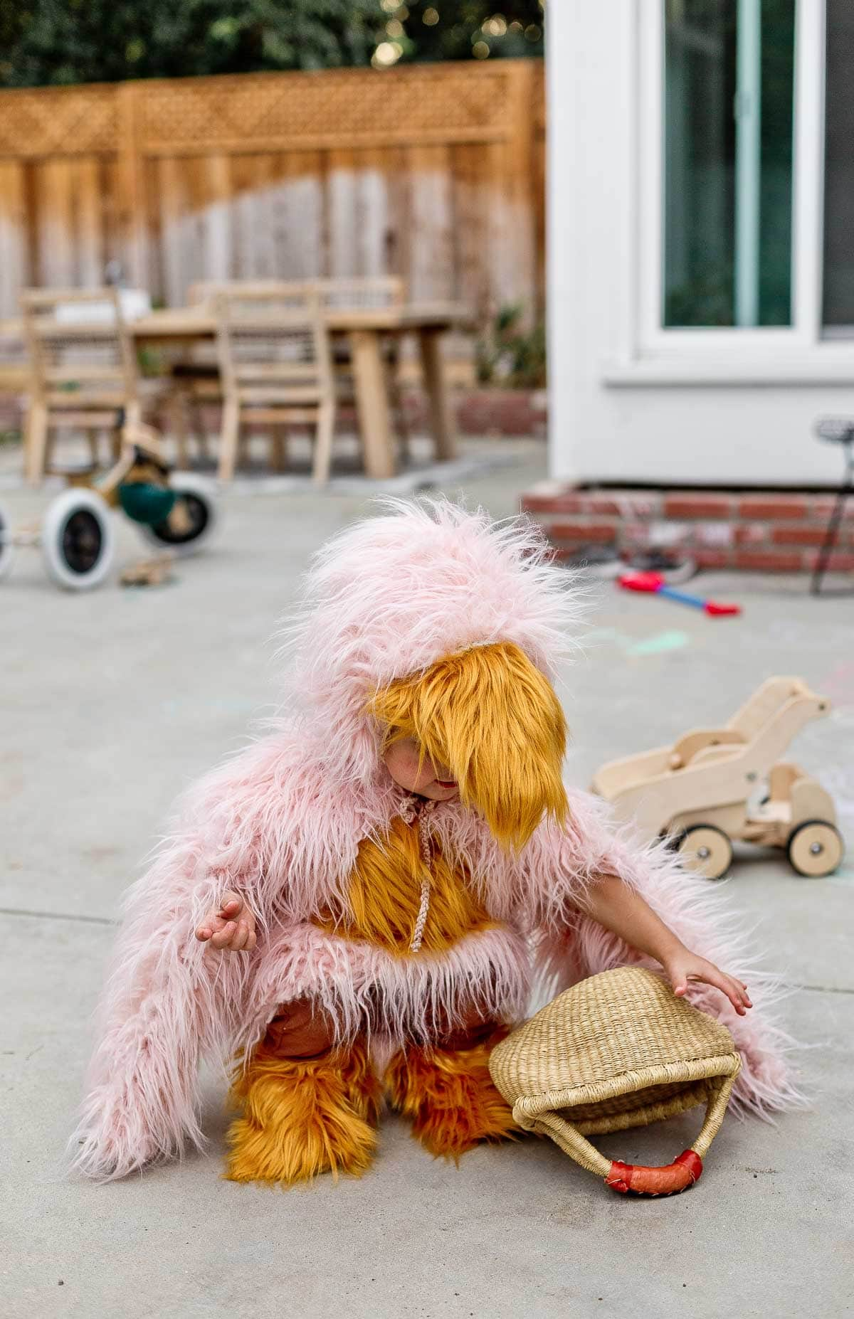 Child wearing handmade bird costume, playing in the backyard.