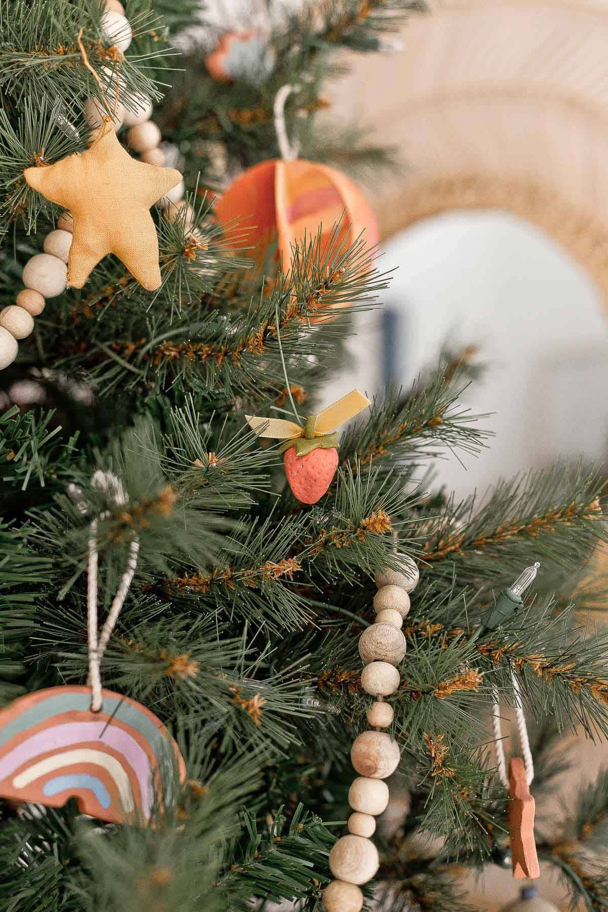 Closeup image of a Christmas tree with handmade ornaments and wood garland.