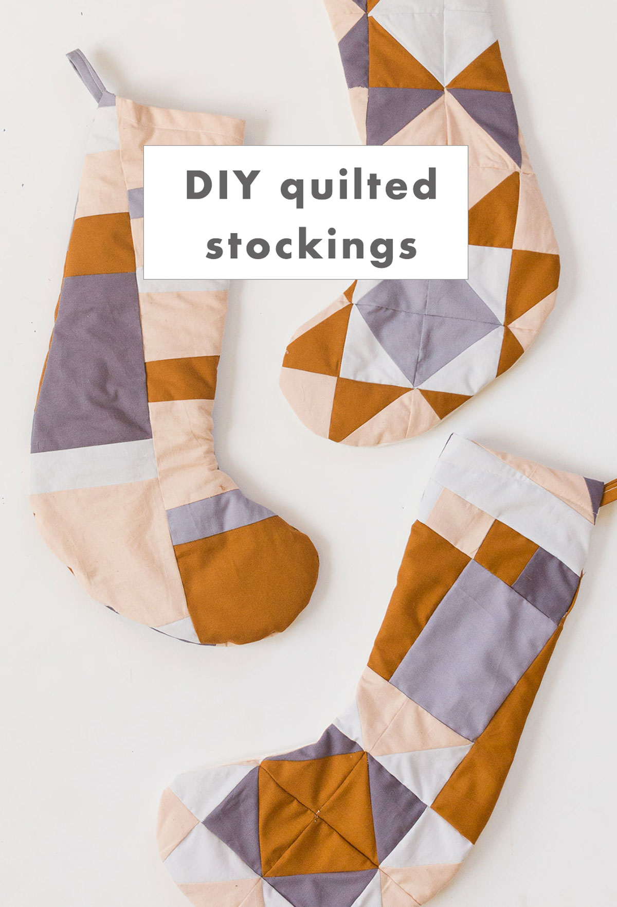 Three quilted Christmas stockings laid out on a white background.