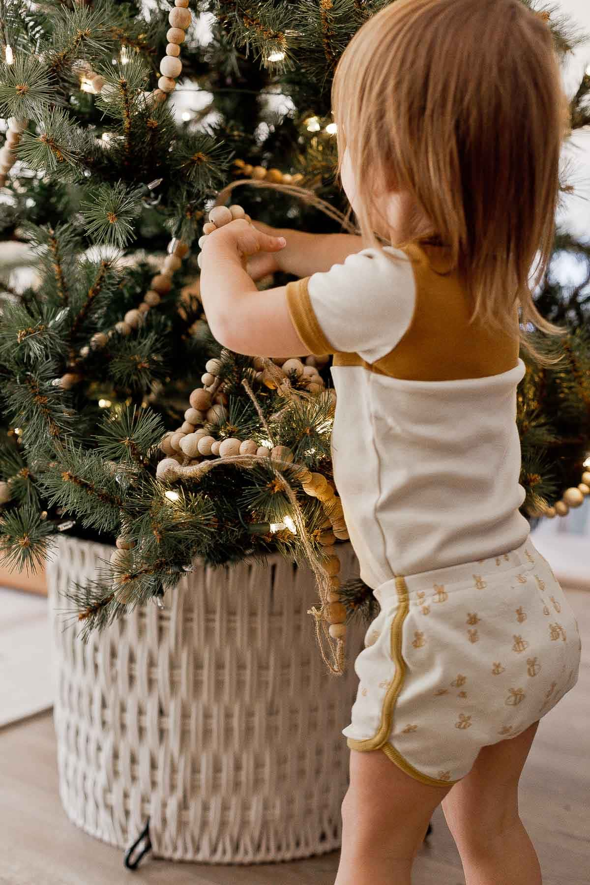 Child decorating a Christmas tree with wood garlands.