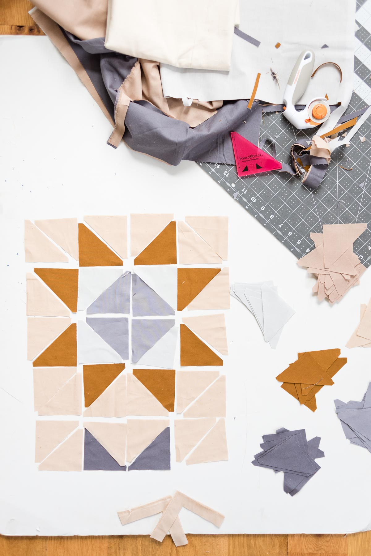 Cutting quilting triangles out of fabric into a pattern.