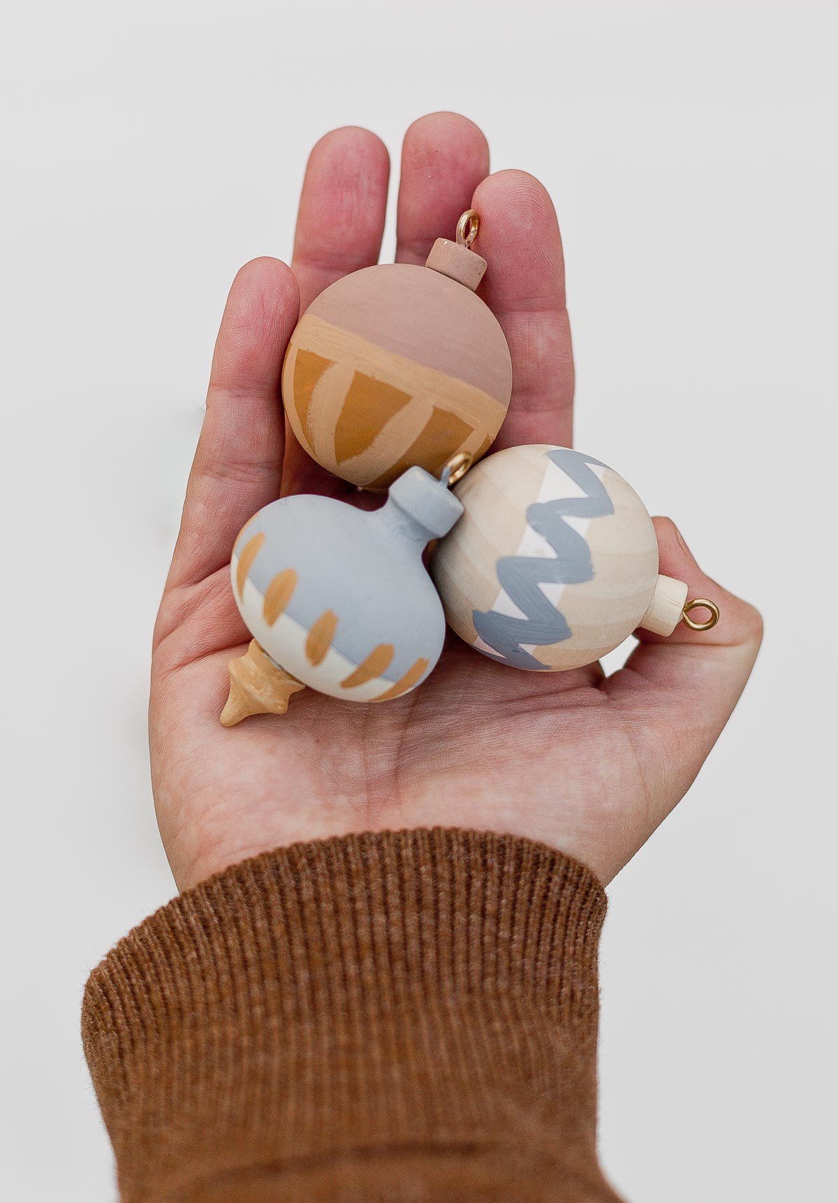 Holding DIY painted wood ornaments in the hand.