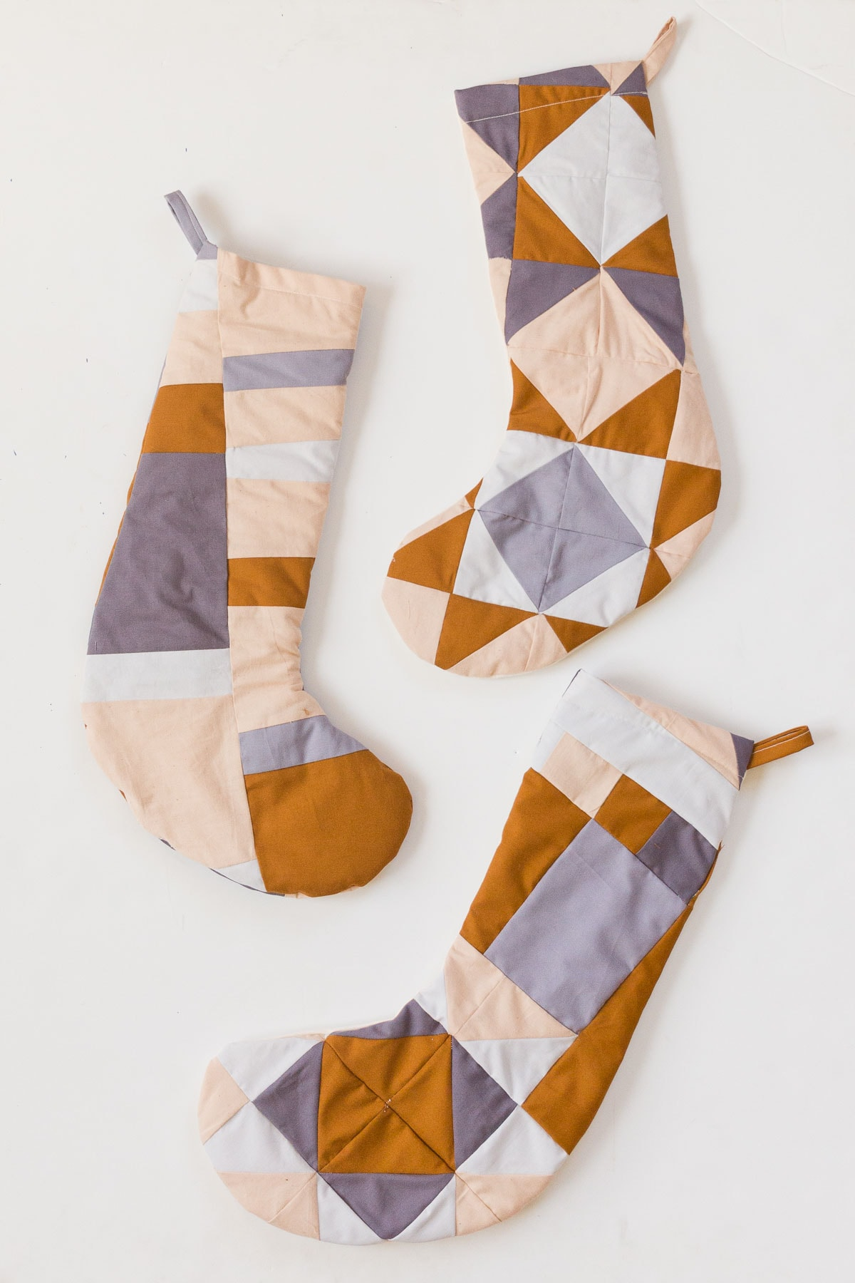 Earth-toned Christmas stockings in various quilted patterns.