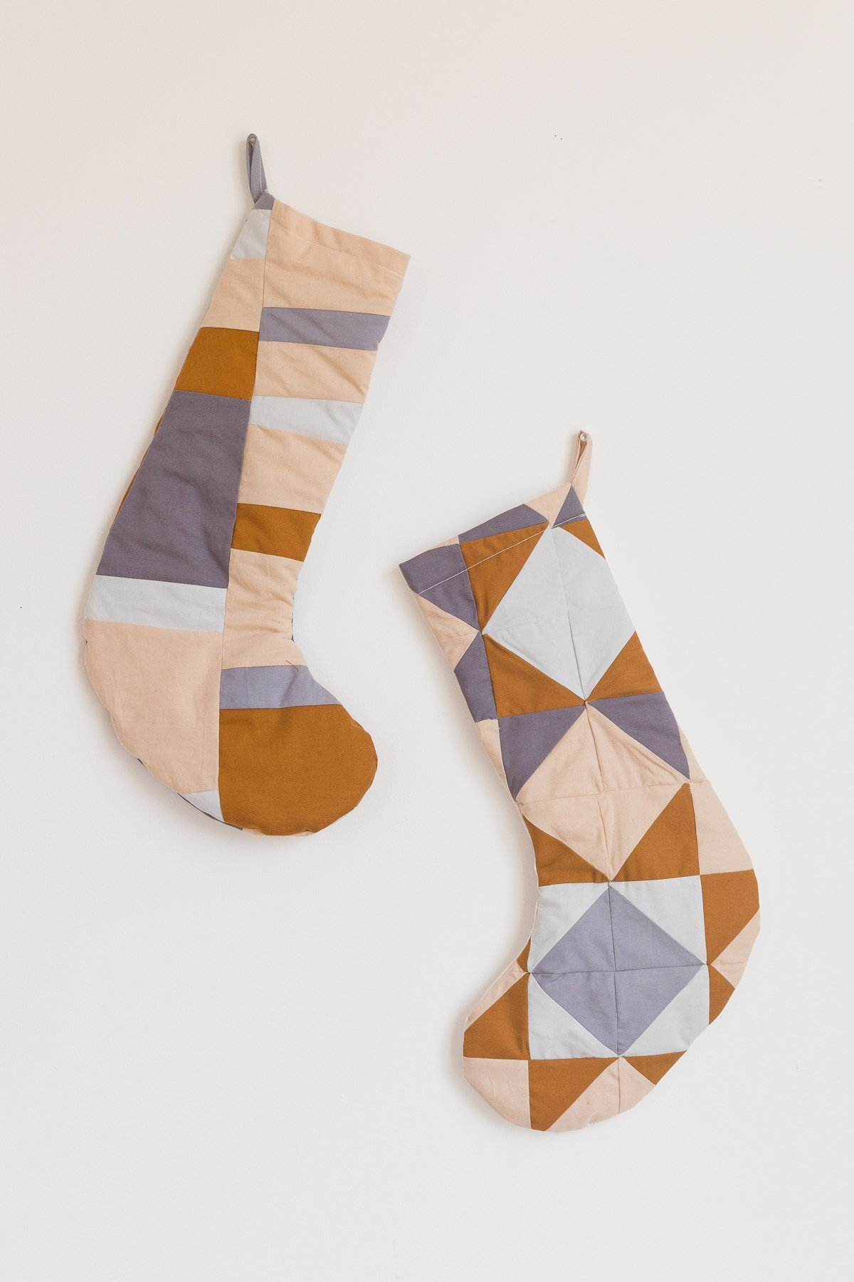 Quilted Christmas stockings in neutral, earthy colors.