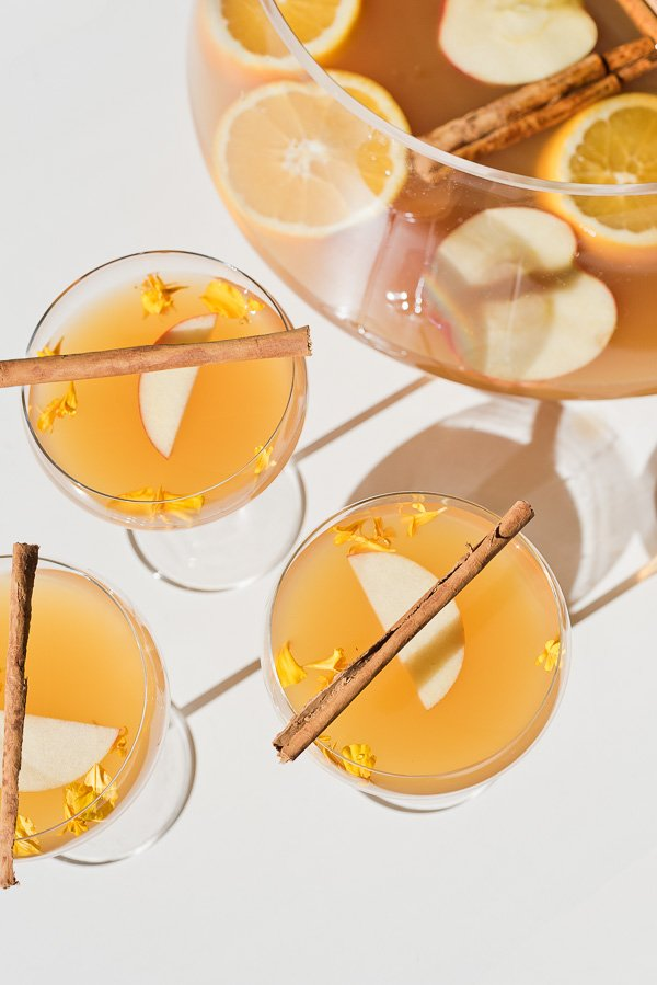 A spiked cider cocktail recipe in coupe glasses with cinnamon sticks on top