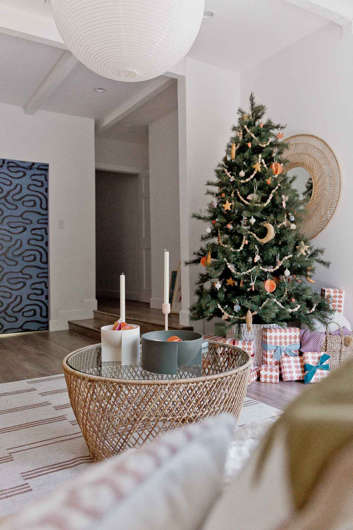 Large Christmas tree in the corner of a modern boho living room.