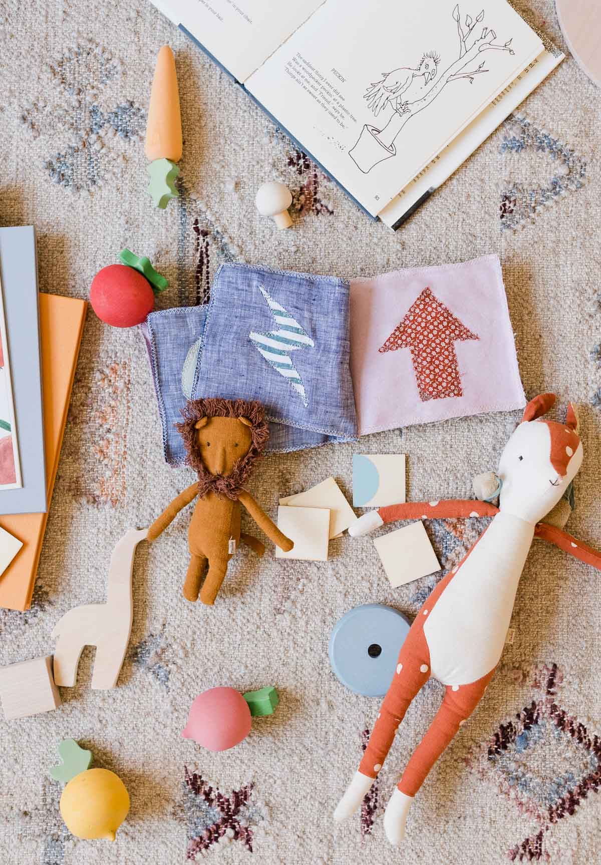 Kids toys and a soft sewn book on the floor