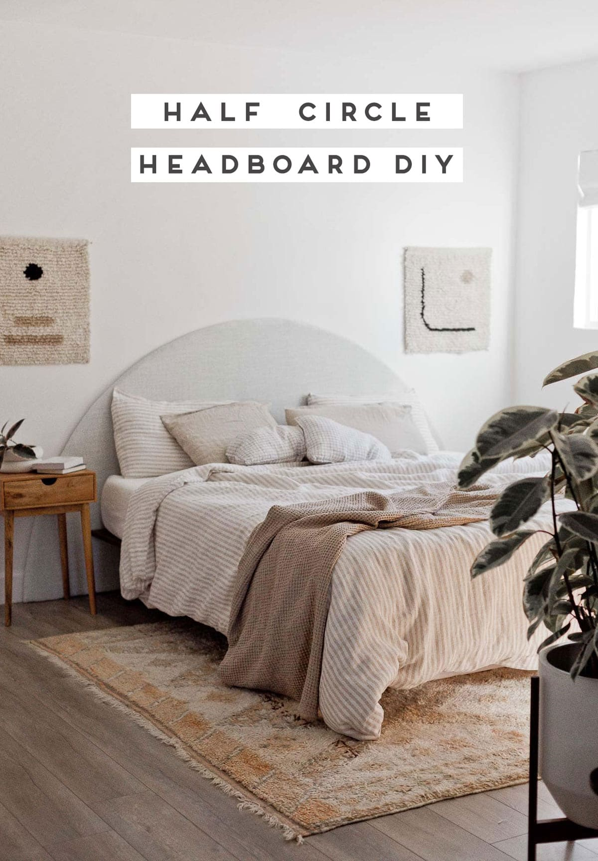 Neutral modern bedroom with a half circle headboard and striped neutral bedding.